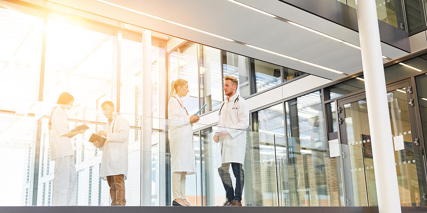 Two groups of four healthcare professionals standing in a hallway discussing