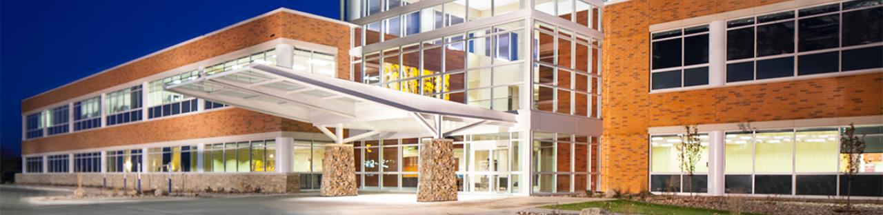 Exterior of a tan brick Hospital building entrance at night