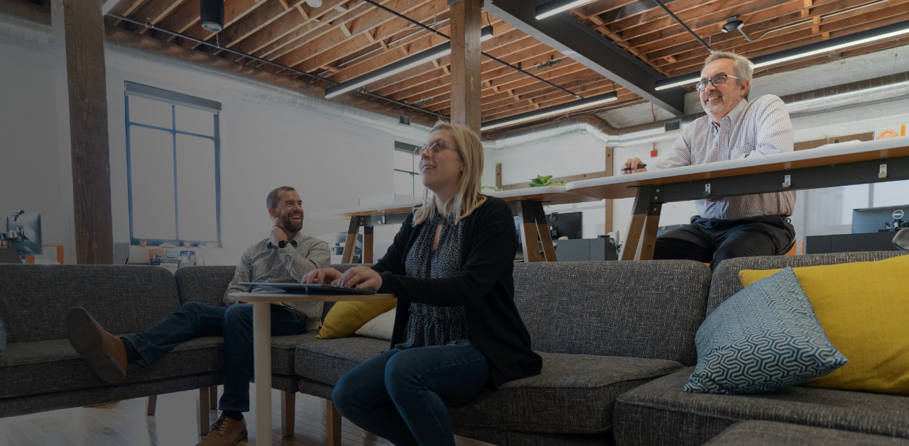 Two men and a woman sitting in an office space discussing
