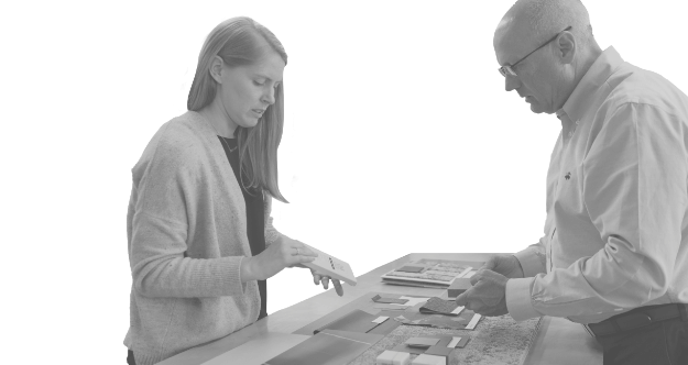 A man and women standing around a table together handling material samples